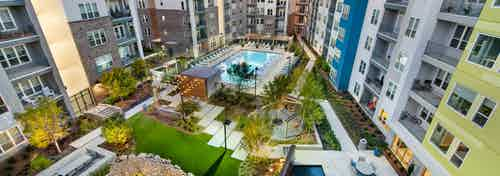 AMLI Piedmont Heights courtyard with large pool and lounge chairs surrounded by lit green areas and foliage at dusk