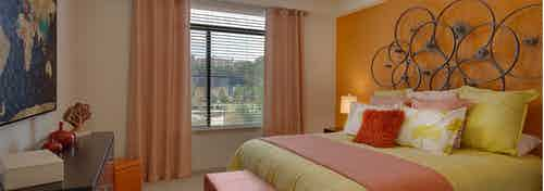 AMLI Ponce Park bedroom with a pink and yellow bed under circular art piece hanging on bright orange wall with a large window