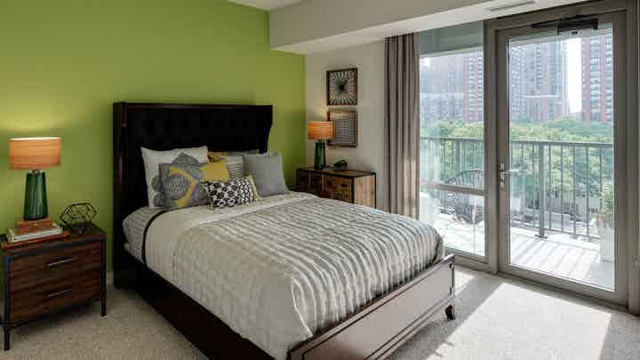 Furnished bedroom with lime green wall and queen sized bed at AMLI 900 with floor to ceiling windows and private balcony.