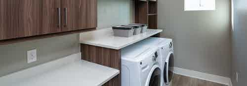 Interior view of AMLI South Shore in unit washer and dryer tucked under a raised cabinet with a white countertop