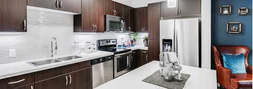 Interior view of a kitchen at AMLI Cherry Creek apartments with an island and white granite counter top and living room chair