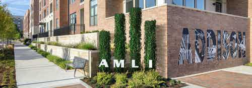 AMLI Addison orange brick building with four pristinely landscaped shrubs with letters spelling AMLI next to a wall mural