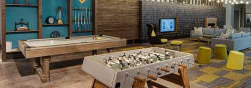 Modern clubroom at AMLI Lofts with billiard and foosball tables and a seating area with a large TV in the background