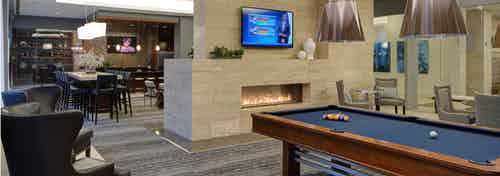 Clubroom at AMLI River North with billiards and a large fireplace as well as a flat screen TV and multiple seating options