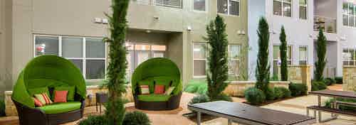 Close up of covered green moon chairs with colorful pillows in the courtyard at AMLI at Mueller apartment community