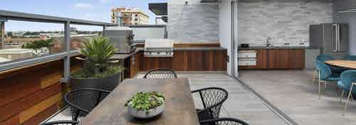 Exterior daytime view of rooftop lounge with BBQ grill and pizza oven and tables and chairs overlooking the city