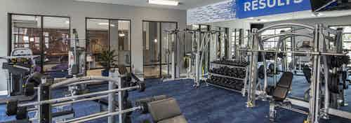 Fitness center at AMLI Eastside apartments with strength training  machines and a dumbbell rack set on patterned blue carpet