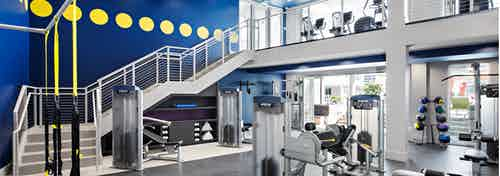 Interior of two-story fitness center at AMLI Lex on Orange apartments with TRX system and medicine balls and cardio machines