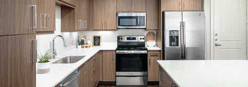Interior close up of spacious AMLI Addison island kitchen with sleek quartz countertops and light wood cabinets