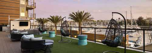 Daytime view of lounge with teardrop hanging chairs and big screen TV overlooking marina at AMLI Marina Del Rey apartments