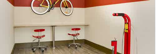 AMLI Ponce Park apartment bike repair room with large table set up for all bike repair needs and air pump for bike tires