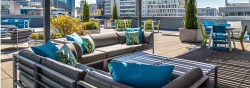Daytime view of rooftop deck with outdoor patio furniture plants and view of Seattle