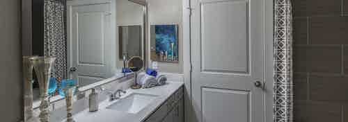 AMLI Eastside apartment bathroom with quartz countertops and large mirror and lights above and closed door and garden tub