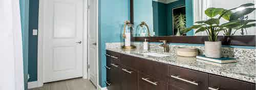 Interior view of a bathroom at AMLI Joya apartment with double sink vanity, large mirror on wall and granite counters