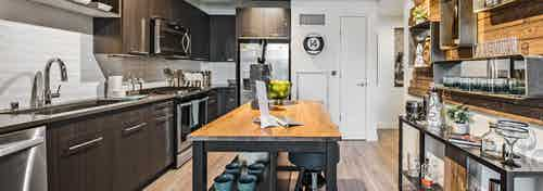 Interior view of apartment of AMLI Arc of kitchen with dark cabinets stainless steel appliances and entry way