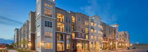 Exterior rendering of AMLI RidgeGate apartment building main entrance with lit windows and patios and trees and cars at dusk