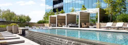 AMLI Fountain Place pool with infinity edge waterfall cascading on grey stones with grey lounge chairs and private cabanas