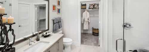 AMLI Buckhead bathroom with a vanity sink and clear glass door leading into the shower with walk in closet door peaking open