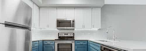 Kitchen at AMLI 535 apartment building with white and blue cabinets and stainless steel appliances with light gray floors