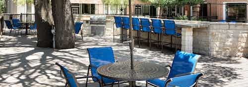 Outdoor barbecue area at AMLI Eastside with round tables and blue chairs with blue barstools at a brick counter in background