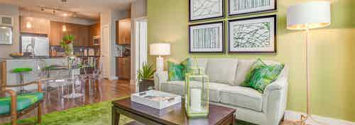 A living room at AMLI Riverfront Park apartments with couches and lamps and a green color scheme with a view into the kitchen
