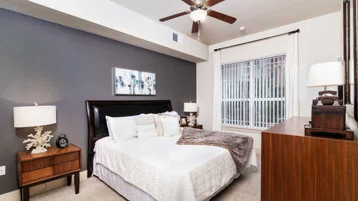 Interior view of a bedroom at AMLI Park Avenue apartments with a bed with black head board and lamps with glass balcony door