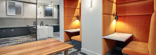 Co working space at AMLI Addison with a long wooden table and two orange nooks with a built in desk and booth seating