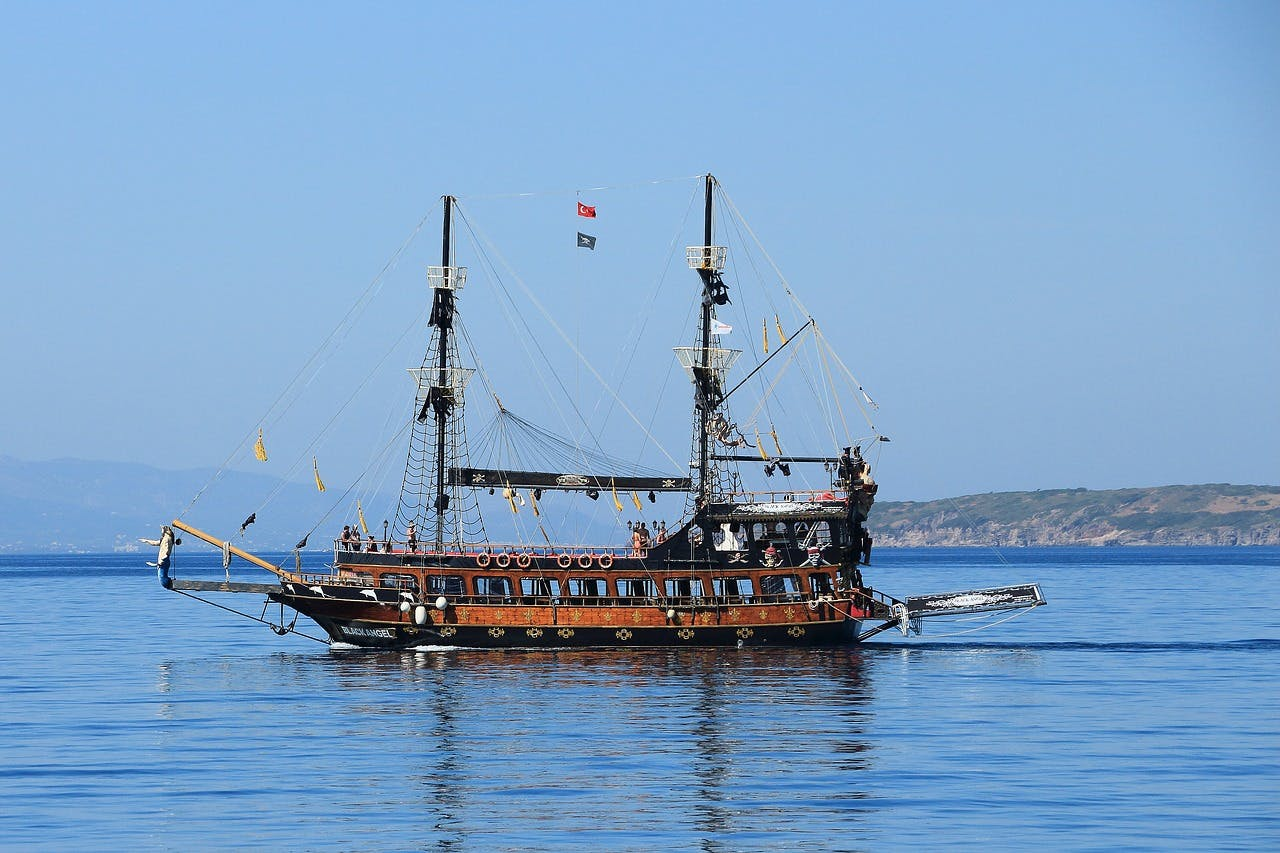 A two-masted pirate ship with sails down on the water.