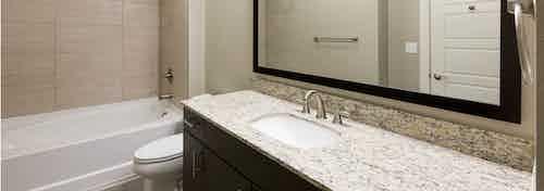 AMLI Covered Bridge bathroom with elegant granite countertop and white oversized bath tub with  tile surround