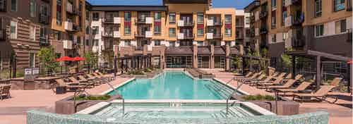 Exterior view of the pool area at AMLI Cherry Creek apartments with a hot tub and lounge chairs and tables with umbrellas