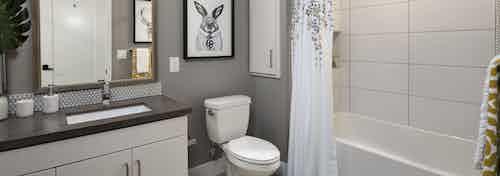 Interior of AMLI Marina Del Rey apartment bathroom with grey quartz countertop and soaking tub, tile surround and soap niche