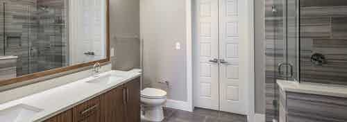 AMLI South Shore apartment bathroom with glass shower with tan tile surround and double vanity with brown wood cabinets