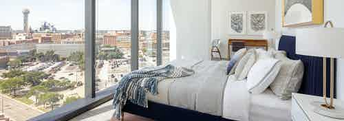 Interior view of AMLI Fountain Place apartment bedroom with navy blue bed facing large wall of windows and view of Dallas