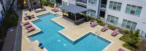 Aerial view of courtyard pool at AMLI South Shore apartments with a covered grill area and surrounding burgundy lounge chairs