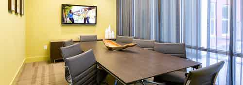 AMLI at Mueller conference room with yellow walls and light flooring with a long desk and office chairs near tall windows