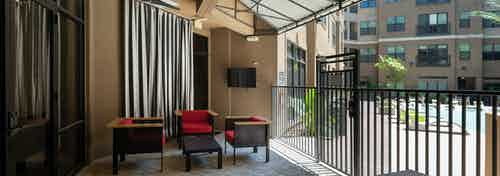 AMLI Uptown aqua lounge overlooking the courtyard pool featuring outdoor HDTV and seating areas with red cushions