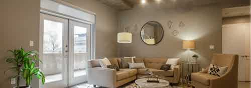Interior of AMLI Downtown living room with neutral colored seating in front of balcony doors with bright daytime view