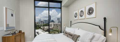 AMLI Lenox bedroom with floor to ceiling windows and a bed with a white comforter and bedside nightstands with lamps