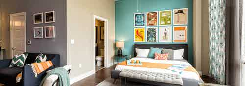 AMLI at Mueller bedroom with a teal accent wall and colorful wall art hanging above bed with peek into connecting bathroom