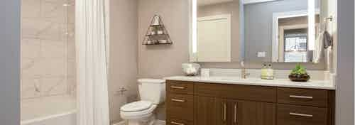 Interior of AMLI Downtown bathroom with shower tub with marble wall tile and a toilet next to a long dark wood vanity sink