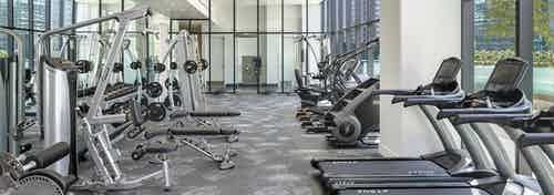 Interior view of fitness center at AMLI Fountain Place apartment building with tread mills, weight machines and large windows