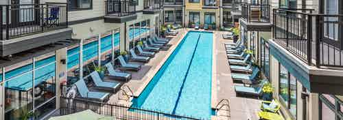 Exterior view of AMLI 5350 pool area with two long thin swimming pools separated by blue lounge chairs on cement