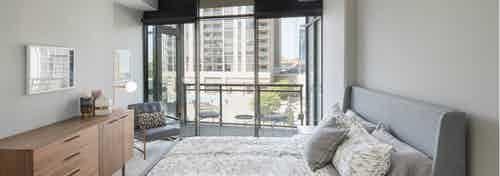 AMLI Arts Center bedroom with neutral walls and white patterned bedding with bright city view out of floor to ceiling windows