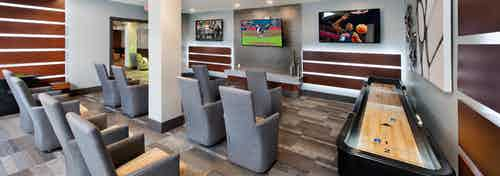 Interior view of the media room at AMLI Piedmont Heights with grey seating facing multiple large TVs on the wall