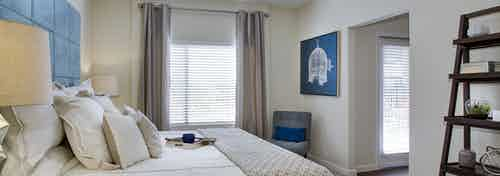 AMLI Ponce Park apartment bedroom with cream walls and dark hardwood flooring with large windows for natural sunlight