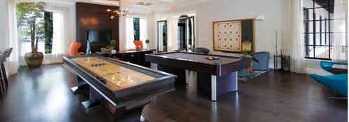 Interior clubroom at AMLI Toscana Place with billiards and shuffleboard table, large wall scrabble game, TV and seating area