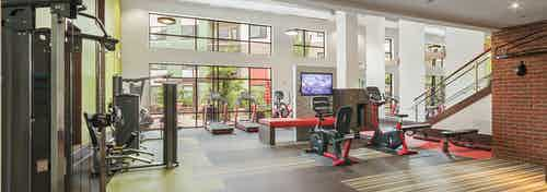 Interior of the fitness center at AMLI Ponce Park apartments with multiple treadmills and exercise bike and weight machines