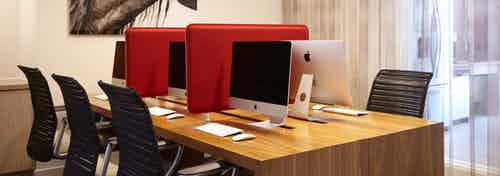 AMLI on Riverside business center with long wooden desk with black office chairs and Apple computers with bold red separators