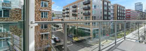 A large apartment balcony at AMLI 535 with glass door with views of South Lake Union with cars on the street and blue sky