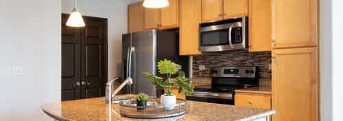Interior view of AMLI 300 apartment kitchen with an island, custom wood cabinetry and stainless steel appliances